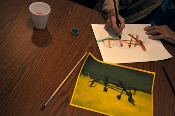 A woman makes a watercolor painting based off a photo of a Mark Di Suvero sculpture currently installed at Franconia.